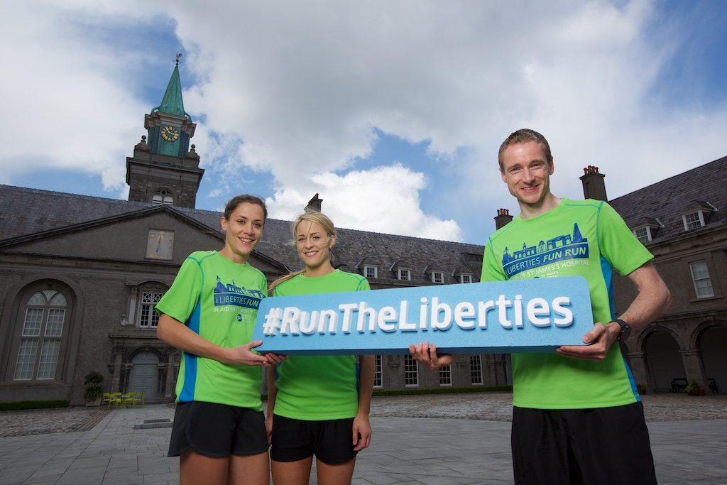 Photo of 3 people holding the Liberties Fun Run banner